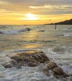Sea wave and rock sunset Stock Photos