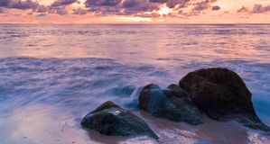 Sea wave on the rock at sunset Stock Image