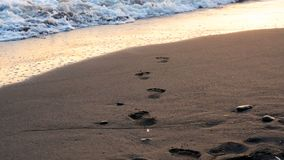 Sea wave rolls ashore Human footprints in the sand close-up sunrise or sunset time, low angle view, slow motion camera stock video