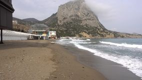 The sea wave runs on the deserted pebble coast of the Black sea. Cloudy spring day in the village of Novy Svet in the Crimea stock footage