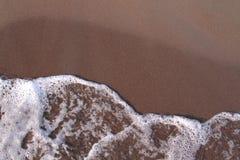 Sea wave on the sand beach Stock Photos
