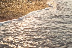 Sea wave on sand and stone at sunrise Stock Images