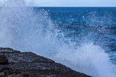Sea wave slamming on the rocks. Of the coastline Royalty Free Stock Image