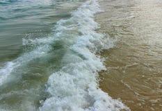 Foam with a sea wave on a sand beach stock photo