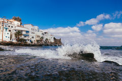 Sea wave with splashes and white houses Royalty Free Stock Photography