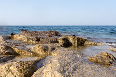 Sea wave splashing over the shore rocks with a high sea spray Royalty Free Stock Photo