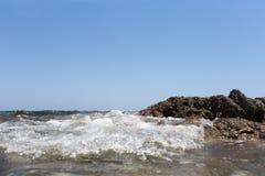 Sea wave splashing over the shore rocks with a high sea spray Stock Photo