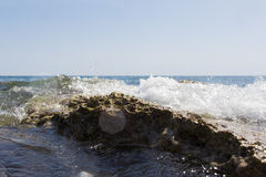 Sea wave splashing over the shore rocks with a high sea spray Royalty Free Stock Image