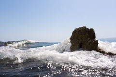 Sea wave splashing over the shore rocks with a high sea spray Stock Images