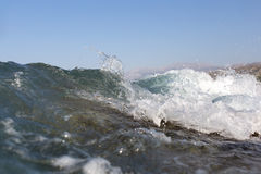 Sea wave splashing over the shore rocks with a high sea spray Royalty Free Stock Photography
