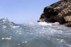 Sea wave splashing over the shore rocks with a high sea spray Stock Photography