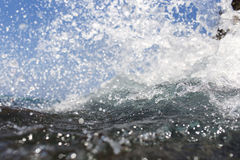 Sea wave splashing over the shore rocks with a high sea spray Stock Image