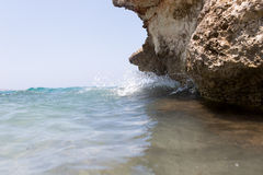 Sea wave splashing over the shore rocks with a high sea spray Stock Photos