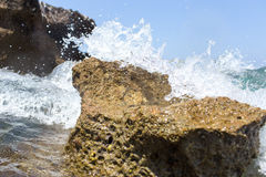 Sea wave splashing over the shore rocks with a high sea spray Royalty Free Stock Images