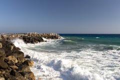 Sea wave splashing over the shore rocks with a high sea spray Royalty Free Stock Photos