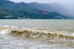 Sea wave in stormy weather. The turbid wave. Low clouds over the coast. Montenegrin beach in rainy weather. The sea and mountains Royalty Free Stock Photography