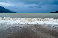 Sea wave in stormy weather. The turbid wave. Low clouds over the coast. Montenegrin beach in rainy weather. The sea and mountains Stock Photo