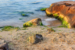 Sea wave strugle with stone on the sandy beach Stock Image
