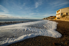 Sea wave surf and foam on sandy empty foam beach and nice blue sky. Wide angle view Stock Photos
