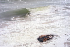Sea wave surf and wild stone on sandy beach in swirling water Royalty Free Stock Photography