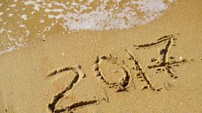 Sea wave washes off in 2017 and 2018 appears. New Year 2018 is coming concept - write 2018 on a beach sand background. Sea wave washes off in 2017 and 2018 stock footage