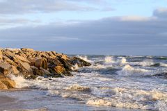 Sea with waves against a cloudy sky stock image