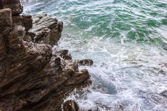 Sea waves against rocks. Blue and green sea waves splashing against rocks Stock Photo