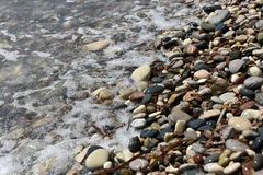 Sea waves approaching pebble stones Royalty Free Stock Photography