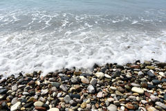 Sea waves approaching pebble stones Royalty Free Stock Images
