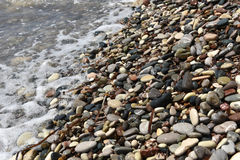 Sea waves approaching pebble stones Royalty Free Stock Image