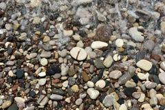 Sea waves approaching pebble stones Stock Photos