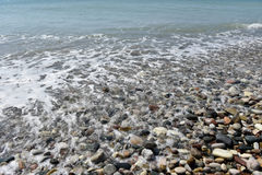 Sea waves approaching pebble stones Stock Images