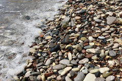 Sea waves approaching pebble stones Royalty Free Stock Photo