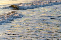 Sea waves background. Calm seascape of waves splashing on the beach on sunrise with copy space Royalty Free Stock Photos