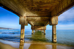 Sea waves and the beach under the old pier Stock Image