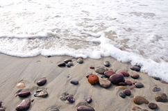 Sea waves beat stones lying in sand on coast line. Royalty Free Stock Photo