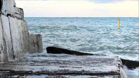 The sea waves are beating against concrete pier. stock footage
