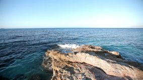 Sea waves are beating against the stone shore. Greece. Wave splash beautiful turquoise blue water slow motion rocks sandy beach breeze summer holiday touristic stock video