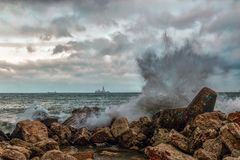 The sea waves break against the rocks on the shore. In the distance you can see the ship Royalty Free Stock Photo