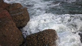 Sea waves break on the rocky stones on the beach. Slow motion. Sea waves break on the rocky brown stones on the beach turning into a fine spray. Slow motion stock footage