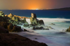 Sea waves breaking onto rocks at night. Long exposure night shot of sea waves breaking at a cliff in Sozopol, Bulgaria. Distant city lights across the bay, view Royalty Free Stock Photos