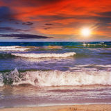 Sea waves breaking on the sandy beach at sunset Stock Images