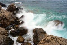 Sea waves breaking on a stony shore Stock Photos