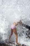 Sea waves breaks over a young girl Royalty Free Stock Photo