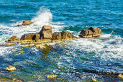 Sea waves breaks about rocky shore. Sea waves attacks the boulders of rocky shore and is broken about them stock image