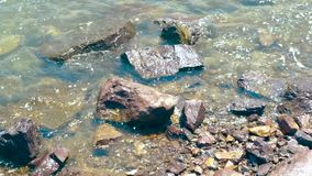 Sea waves of clear water on rocky beach. Transparent ocean water on stony shore background. Sea waves of clear water on rocky beach. Transparent ocean water on stock footage