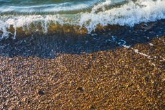 Sea waves on the coast of pebbles at sunrise royalty free stock images
