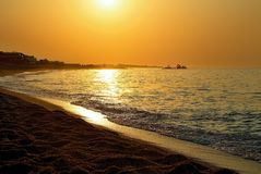 Sea waves in the colors of sunrise on the coast of Costa del Maresme. Beautiful sunrise over the Mediterranean Sea in Stock Image