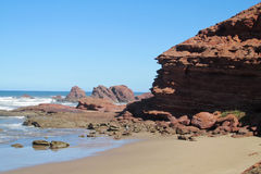 Sea waves coming to the red rocks on the shore Royalty Free Stock Photography
