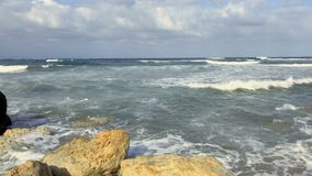 Sea waves covers the beach and breaks on the stones. View of beautiful blue sea with cloudy sky. Waves covers the beach and breaks on the stones. Silence and stock video footage